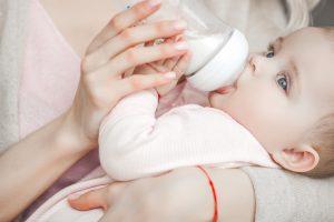 Ребенок есть молочную смесь из бутылочки